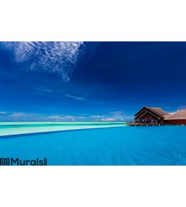 Infinity pool over tropical lagoon with blue sky Wall Mural